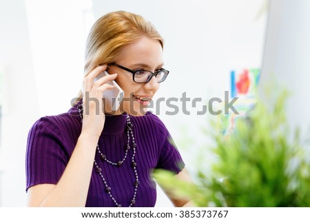 Business woman in office holding mobile phone