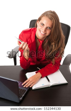 Business woman in red dress working on laptop and talking on cellphone