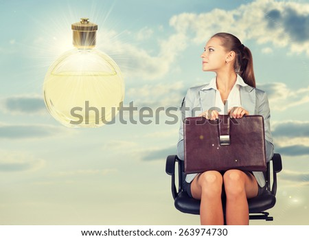 Business woman in skirt, blouse and jacket, sitting on chair and holding briefcase imagines perfume. Against background of sky and clouds - stock photo