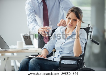 Business woman in wheelchair having an headache at office, her collegue is giving her a glass of water and helping her - stock photo