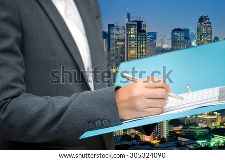 Business woman inspect a document with blur city night background  - stock photo