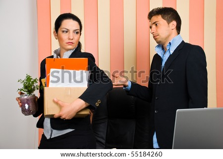 Business woman is dismissed  by her boss and invited to leave the office with her assets in a carton box - stock photo