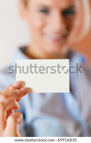 Business woman is handing her business card over â?? focus on the card - stock photo