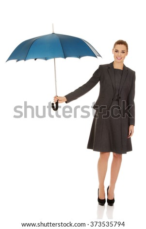 Business woman is holding blue umbrella - stock photo