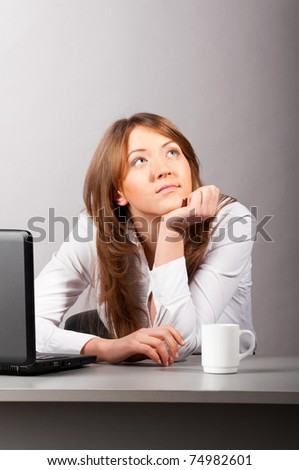 business woman is sitting in the office with laptop and thoughtfully looking sideways