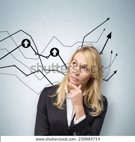 Business woman is standing in front of a chart on the concrete wall.  - stock photo