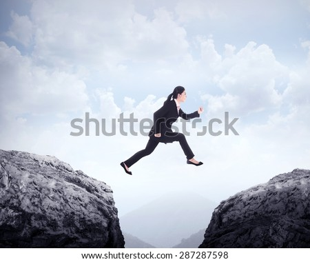 Business woman jumping across hill. Business challenge conceptual - stock photo