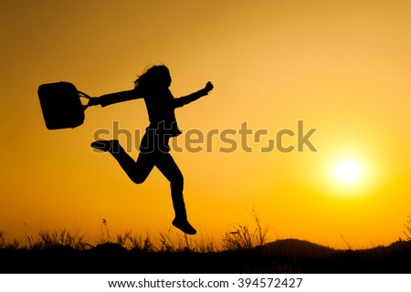 Business woman jumping and holding bag  sunset silhouette.Copy Space