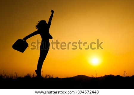Business woman jumping and holding bag  sunset silhouette.Copy Space - stock photo