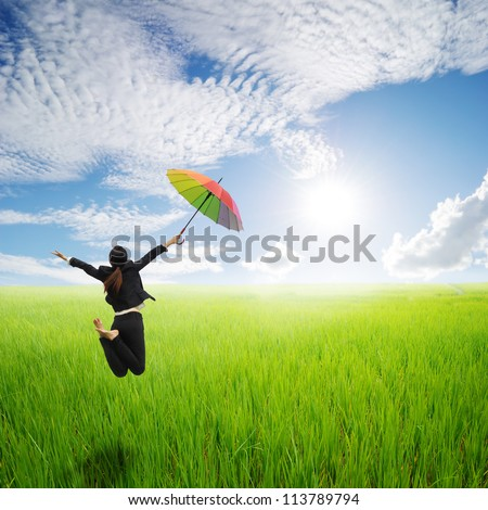 Business woman jumping holding rainbow umbrella in green rice fields and sunset