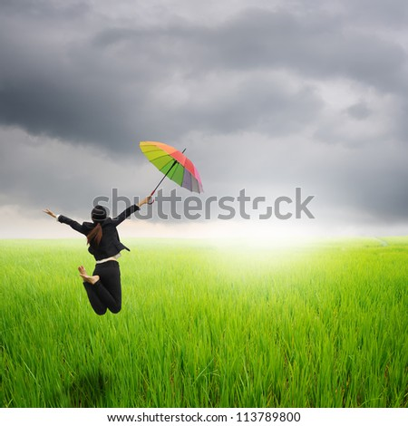 Business woman jumping holding rainbow umbrella in green rice fields and sunset - stock photo