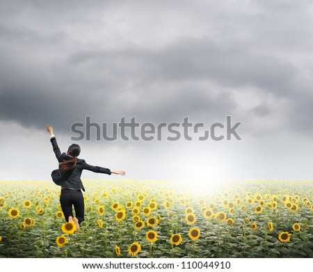 Business woman jumping in  rainclouds over sunflowers field