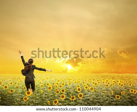 Business woman jumping in  sunset over sunflowers field