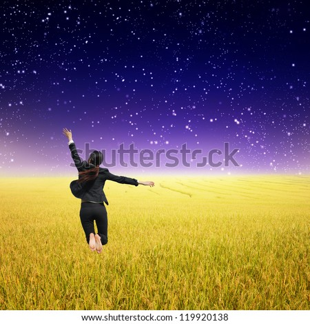 Business woman jumping in Yellow Rice fields and rainclouds - stock photo