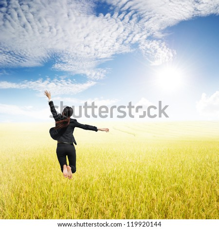 Business woman jumping in Yellow Rice fields and sun sky - stock photo