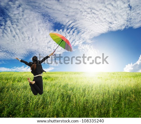 Business woman jumping to blue sky in grassland with rainbow umbrella - stock photo