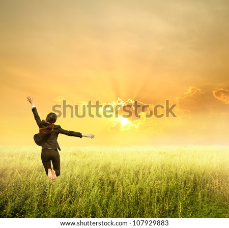 Business woman jumping to sunset in grassland