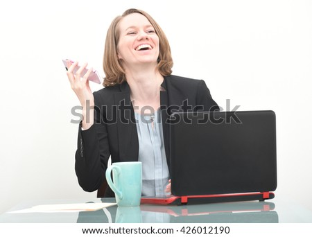 Business woman laughing while on her cell phone - stock photo