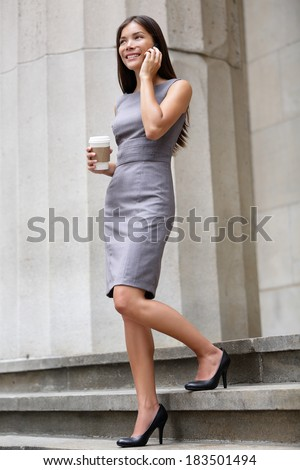 Business woman lawyer professional walking outdoors talking on cell smart phone drinking coffee from disposable paper cup. Multiracial Asian / Caucasian businesswoman smiling happy outside. - stock photo