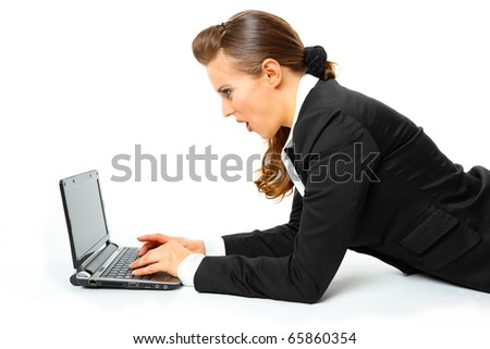 Business woman laying on floor and amazedly looks in laptops screen