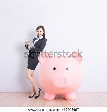 business woman lean pink piggy bank and use digital tablet pc with white wall background, great for your design or text, asian