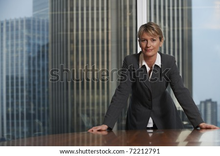 Business woman leaning on chair in boardroom looking at camera - stock photo