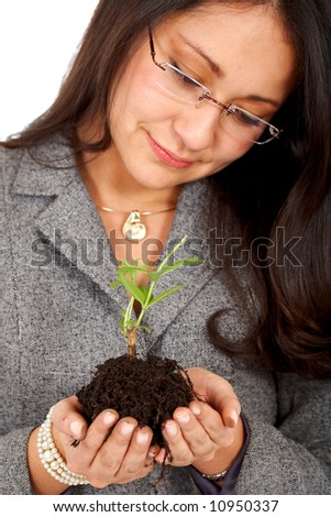 business woman looking after a tree in her hands - stock photo