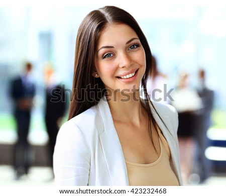 business woman looking at camera with her colleagues in background at office - stock photo