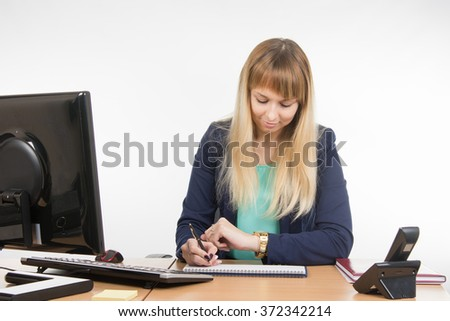 Business woman looking at his watch and schedule of the working day