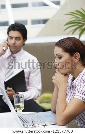 Business woman looking at laptop while colleague talking on cell phone in a restaurant - stock photo