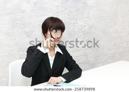 business woman looking into a magnifying glass