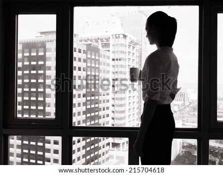 Business woman looking out the window - stock photo