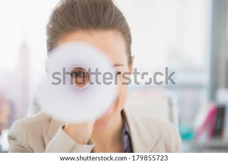 Business woman looking through rolled-up document