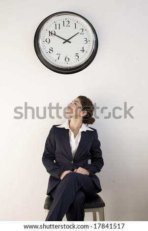 Business woman looking up at wall clock - stock photo