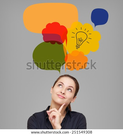 Business woman looking up on idea bulb in color bright bubble on grey background - stock photo