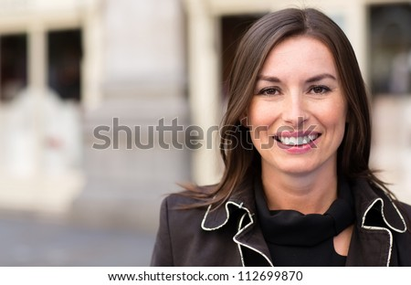 Business woman looking very happy outdoors and smiling - stock photo