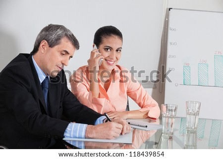 Business woman making a call in a meeting while a manager takes notes - stock photo