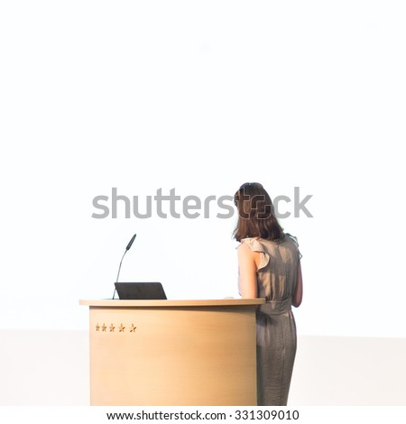 Business woman making business presentation. Female speaker giving a talk at  business conference . Business and Entrepreneurship concept. Brand copy space on white screen. - stock photo