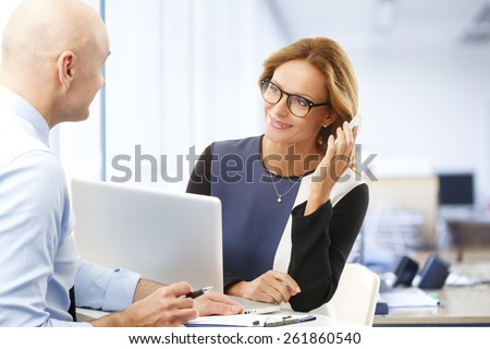 Business woman making call while sitting at meeting with sales man. Teamwork at office.  - stock photo