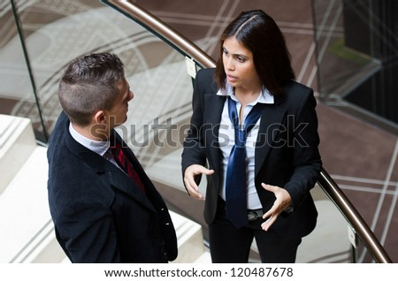 Business woman making gestures while talking to a business man - stock photo