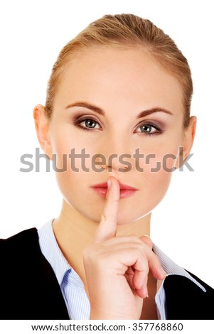 Business woman making silent sign with finger on lips. - stock photo
