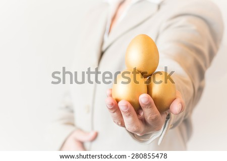 Business woman / man holding golden eggs forward : A golden egg opportunity concept of fortune and a chance to be rich  - stock photo