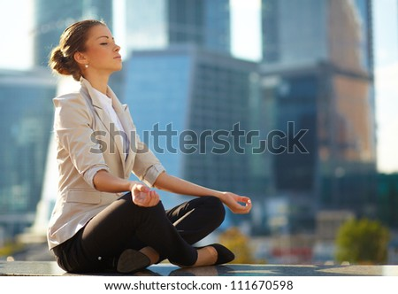 Business woman meditating and making yoga outdoor over building background - stock photo