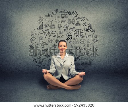 business woman meditating on floor, wall charts and diagrams are drawn - stock photo