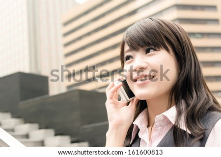 Business woman of Asian talk on cellphone, closeup portrait in urban.