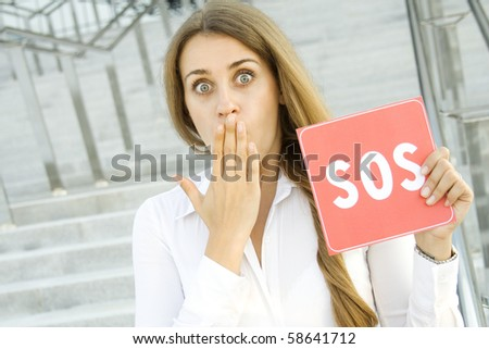 Business woman on a background of office space in the hands holding a red card with the text of SOS. Prayer in aid - stock photo