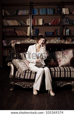 Business woman on a couch holding a tablet PC in his hands. - stock photo