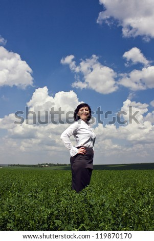 Business woman on a green field. Sunny day outdoors