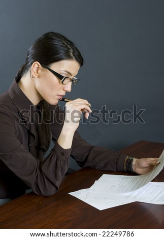 business woman on desk reading