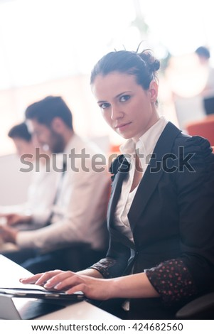 business woman on meeting usineg tablet computer, blured group of people in background at  modern bright startup office interior - stock photo